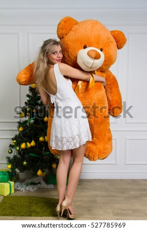 Happy woman received gift a teddy bear. Her beautiful eyes looking at camera. Concept of holiday, christmas.
