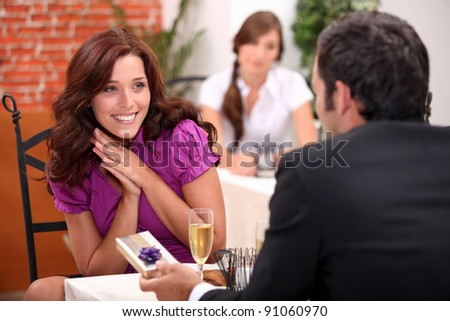 happy woman receiving a gift at restaurant
