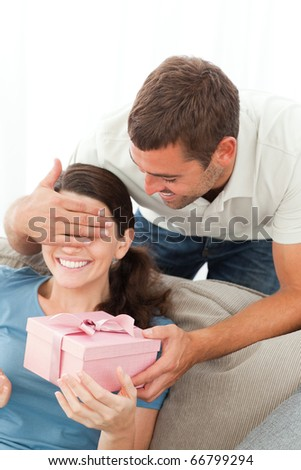 Happy woman receiving a gift from her boyfriend in the living room at home - stock photo