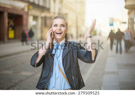 Happy woman receiving good news on the phone in city center - stock photo