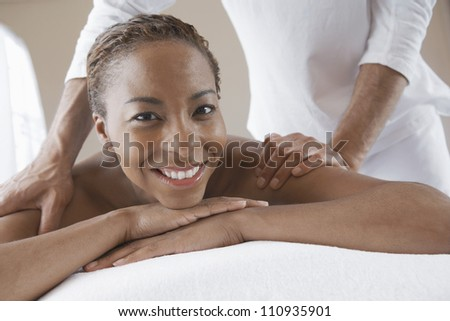 Happy woman receiving shoulder massage at spa - stock photo