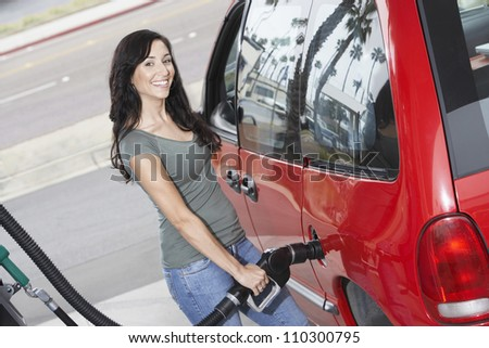 Happy woman refueling her car - stock photo