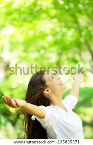 Happy woman rejoice looking up happy enjoying spring or summer forest park smiling with arms outstretched. Beautiful mixed race Asian Caucasian female model. - stock photo