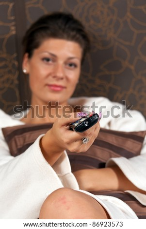 Happy woman relaxing and watching TV - stock photo