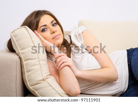 Happy woman relaxing at home lying on bed - stock photo