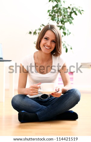 Happy woman relaxing at home with cup of hot coffe - stock photo