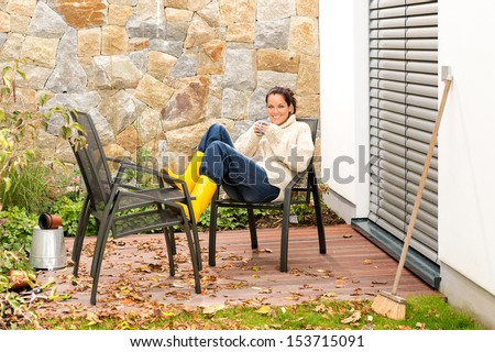 Happy woman relaxing autumn housework drinking coffee fall patio - stock photo