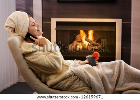 Happy woman relaxing in beauty mask, wearing bathrobe, talking on mobile phone, sitting in cosy living room armchair, in front of fireplace.