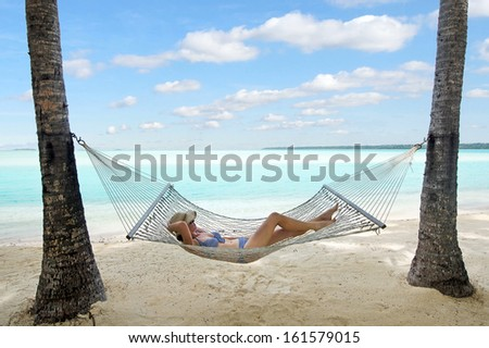 Happy woman relaxing on hammock on the beach during travel vacation on tropical island in Aitutaki lagoon, Cook Islands. - stock photo