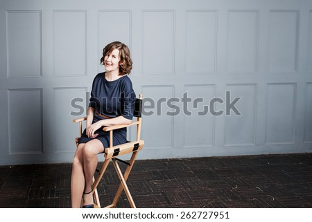 Happy woman relaxing on her chair at home  - stock photo