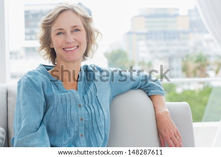 Happy woman relaxing on her couch at home in the sitting room - stock photo