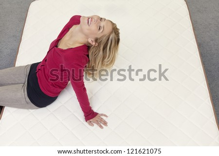 Happy woman relaxing on mattress with head back in furniture store - stock photo