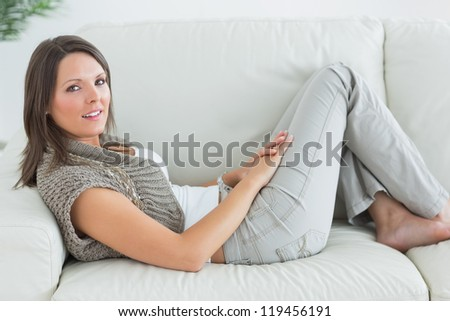 Happy woman relaxing on sofa at home