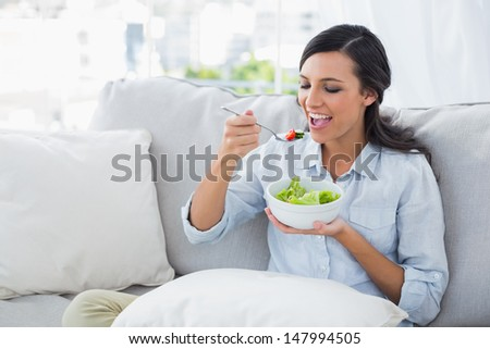 Happy woman relaxing on the sofa eating salad in her living room - stock photo