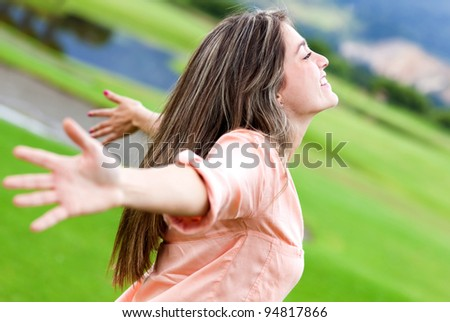Happy woman relaxing outdoors with arms open - stock photo