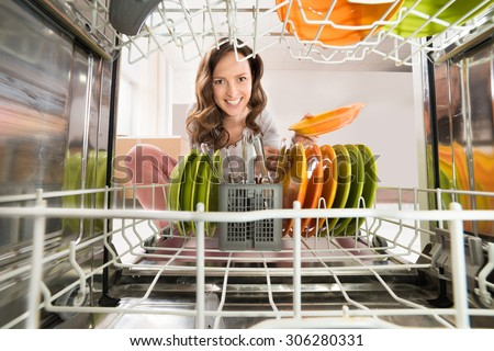 Happy Woman Removing Plate View From Inside The Dishwasher - stock photo