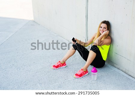 Happy woman resting after running, listening to the music on smartphone - stock photo