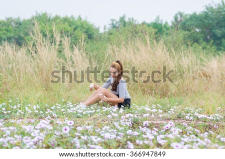 Happy woman resting and relaxing lying down on spring grass and flowers on park outdoor.