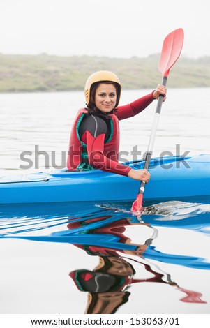 Happy woman rowing on lake in a kayak smiling at camera - stock photo