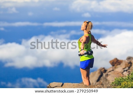 Happy woman runner joyful with arms raised outstretched smiling and ecstatic happiness with eyes closed. Fitness and exercise meditation in summer mountains nature outdoors, freedom concept. - stock photo
