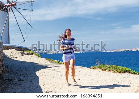 Happy woman running along a coastline near to the windmill.Copy space - stock photo