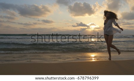 Happy woman running and spinning on the beach near the ocean. Young beautiful girl enjoying life and having fun at sea shore. Summer vacation or holiday. Sunset marine landscape at background.