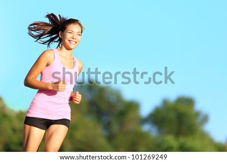 Happy woman running in city park. Asian girl runner jogging smiling aspirational outside on beautiful summer day. Mixed race Asian Chinese / Caucasian female fitness sport model training outdoors. - stock photo