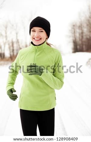 Happy woman running in winter - stock photo