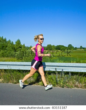 Happy woman running on country road in sunny summer - stock photo