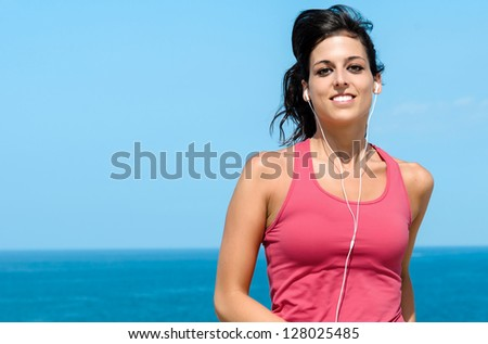 Happy woman running on summer on sea background. Female caucasian fitness athlete jogging. - stock photo