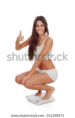 Happy woman saying Ok on a scale isolated on a white background - stock photo