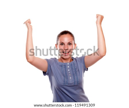 Happy woman screaming and celebrating a victory with arms up looking at you on blue shirt on white background - stock photo