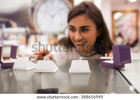 Happy woman selecting a finger ring in a jewelry shop - stock photo