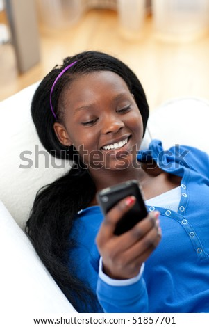 Happy woman sending a text lying on a sofa in the living-room - stock photo