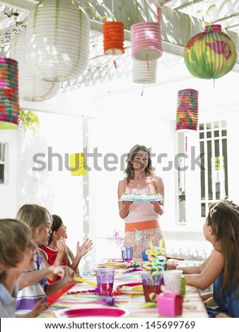 Happy woman serving cake to children at the outdoor birthday party - stock photo