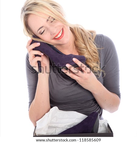 Happy woman shopper caressing a newly purchased and unwrapped shoe with her cheek with a look of bliss isolated on white - stock photo