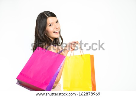 Happy woman shopper with colorful bags full of her recent purchases turning to smile at the camera with a look of satisfaction and pleasure