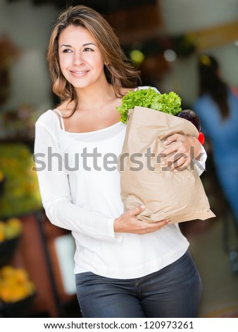 Happy woman shopping carrying a bag with groceries - stock photo