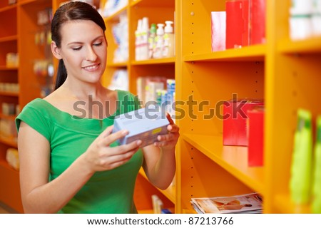 Happy woman shopping for products in a drugstore - stock photo