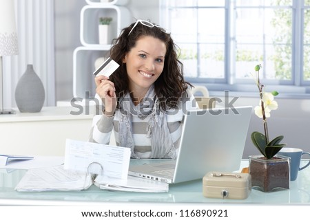 Happy woman shopping on Internet with credit card, smiling at camera. - stock photo