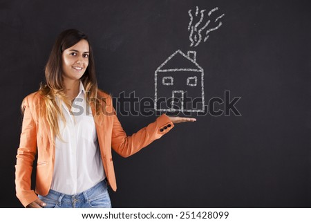 Happy woman showing a house drawing in the chalkboard - stock photo