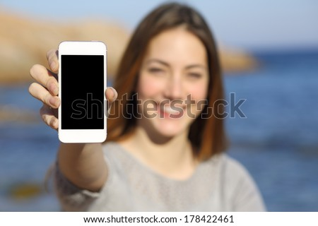 Happy woman showing a smart phone display on the beach with the sea in the background          - stock photo