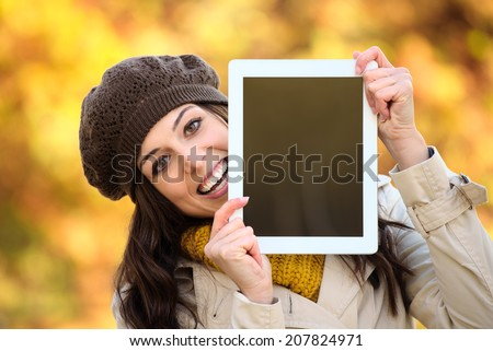 Happy woman showing digital tablet blank screen in autumn season. Brunette caucasian female holding touchpad frame for copy space message or information. - stock photo