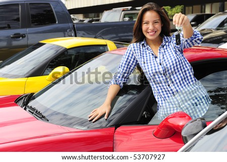 happy woman showing key of new sports car - stock photo