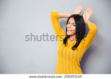 Happy woman showing rabbit ears with her palms over gray background. Looking at camera - stock photo