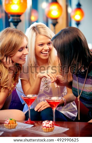 Happy woman showing wedding ring to her friends