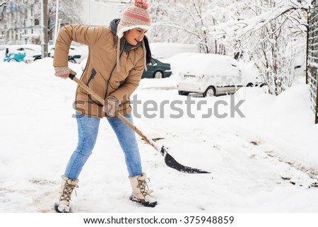 Happy woman showveling snow in parking around house