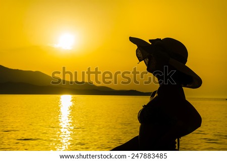 Happy woman silhouette enjoying beach relaxing joyful in summer by tropical water. Beautiful bikini model happy on travel wearing beach sun hat and looking at sea sunset