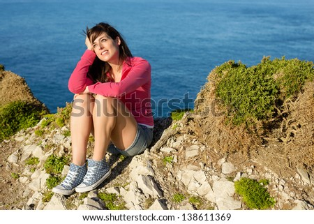 Happy woman sitting and relaxing on sea and coast landscape background. Pensive girl enjoying peace and silence on nature summer vacation. - stock photo