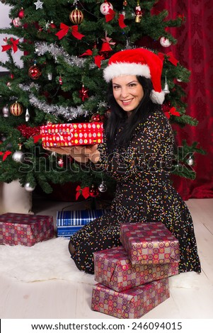 Happy woman sitting down and showing Christmas gifts  near tree - stock photo